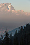 Smoke forms a layer between the forest and the Cascade Mountain range.