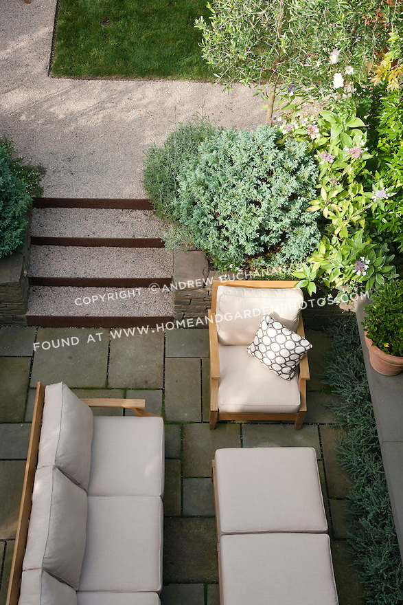 An overhead view of the lower fireplace area and stone steps connecting to the middle lawn area in this multi-level Seattle backyard.