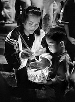 A woman with AIDS and her son prepare a floating lamp during the festival of light in Surin in northern Thailand on October 7, 2000. The floats are sent down the river carrying lights and wishes for the future. Worldwide, more than 20 million people have died since the first cases of AIDS were identified in 1981.