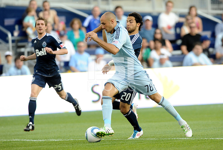 Aurelien Collin (78) defender Sporting KC holds off the challenge of Davide Chiumiento Vancouver Whitecaps... Sporting KC defeated Vancouver Whitecaps 2-1 at LIVESTRONG Sporting Park, Kansas City, Kansas.