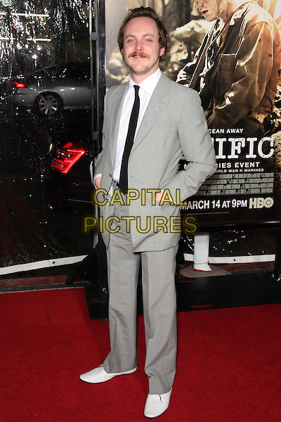 TOM BUDGE.Arrivals to the Los Angeles Premiere of the HBO Miniseries The Pacific at Grauman's Chinese Theatre, Hollywood, CA, USA, February 24th, 2010. .full length moustache mustache grey gray suit tie black white shirt hands in pockets facial hair shoes .CAP/CEL.©CelPh/Capital Pictures.