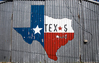 View of a rustic and worn State of Texas Lonestar outline painting on a barn in the Texas Hill Country.