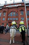 A young boy waiting on the team bus to arrive and having a chat with the mounted police at the front door of Ibrox
