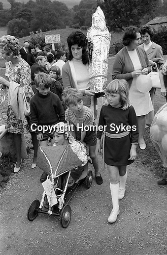 Childrens Fanny Dress Parade during the afternoon. Burning the Bartle, West Witton Yorkshire, England. 1971. Boy in Moon Buggy.