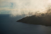Low clouds conceal view over coastline from mountain peak, Lofoten Islands, Norway