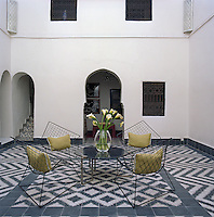 The wire mesh chairs in the courtyard were found in the souk and the black and white tiles are original to the 18th-century riad