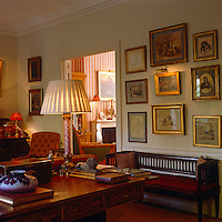 A collection of framed prints hang on a wall above the bench in this sitting room