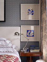 A blue and white colour scheme unites this small apartment punctuated here in the bedroom with the red of an ethnic bed cover