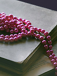 A long pink pearl necklace laid on antique books, with a printed sheet in the first ground.