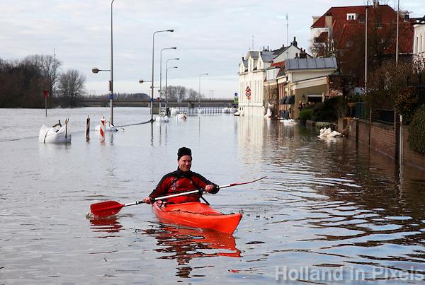 Man vaart in kano op de ondergelopen kade in Deventer