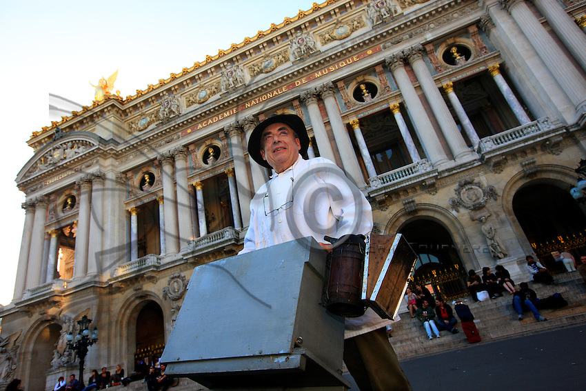 "Paris, Opera Garnier. Jean Paucton, 76 years old, carries a hive in front of the Opera Garnier. ""I have become despite myself the most famous beekeeper in the world. And I began selling at Fauchon by just going to see them. That's how things worked then..My customers are above all seduced by the bit ""Opéra de Paris"". It would work on the Eiffel Tower also. It's a small, inexpensive souvenir. I sell 125 grams for 4.50EUR, that makes 36EUR a kilo. The price for the public reaches 120EUR per kilo, which makes it one of the most expensive honeys in the world."""