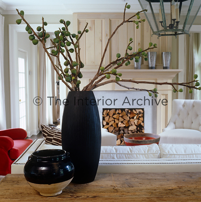 A black Yuan dynasty glazed urn next to a tall vase with fig branches frame the view of the log-filled fireplace in this simple living room
