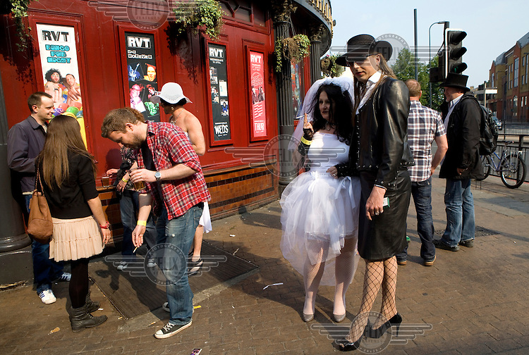 A couple dressed up, one in a wedding dress, stand outside a bar in south London during for a gay marriage fundraiser organized by Outrage! on the day of the Royal Wedding between Britain's Prince William and Kate Middleton.