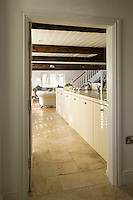 Mellow stone flags lead from a corridor through the kitchen to the living/dining area beyond