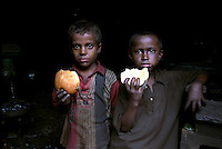 Two child labourers eating their lunch during a break at the factory where they work.