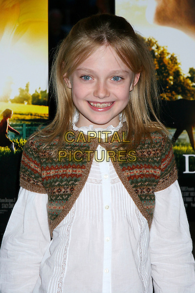 "DAKOTA FANNING .The Premiere of ""Dreamer"" held at the Chelsea West Theatre, New York City..October 17th, 2005.Ref: IW.half length braces shrug white blouse.www.capitalpictures.com.sales@capitalpictures.com.©Capital Pictures"