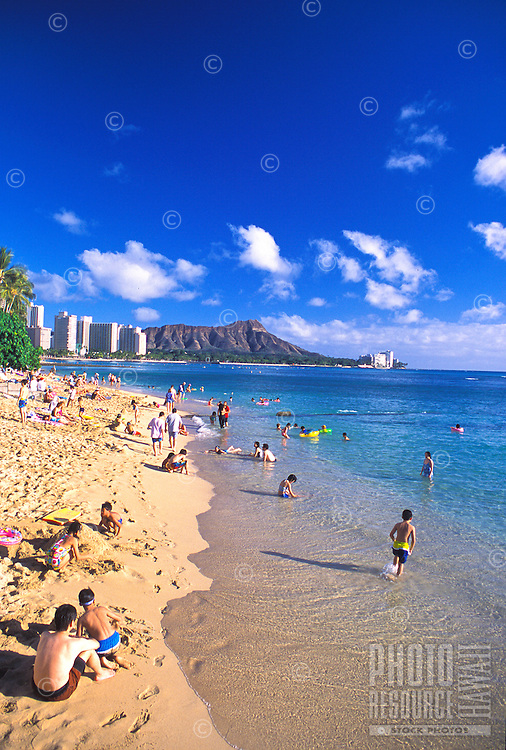 Vacationers from around the world enjoy the sands of Waikiki beach with scenic Diamond Head crater in the background.