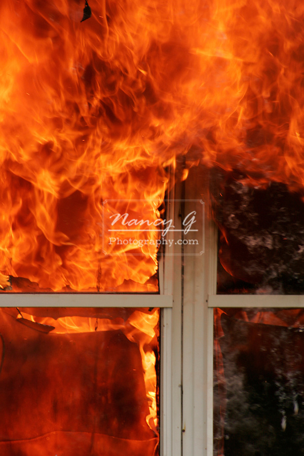 Flames escaping out of the window of a house