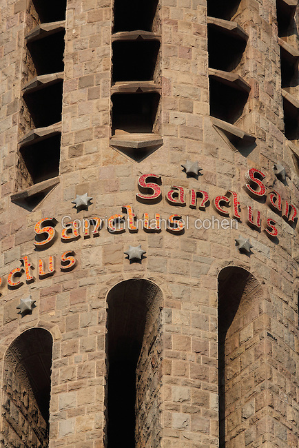 """Sanctus"" repeated nine times in each bell tower of the temple, Passion façade, La Sagrada Familia, Antoni Gaudi, from 1883 to his death in 1926, still incomplete, Barcelona, Spain. The inscriptions use different colours: yellow when dedicated to God father, red when dedicated to God son and orange colour when dedicated to the Holy Spirit. Picture by Manuel Cohen"