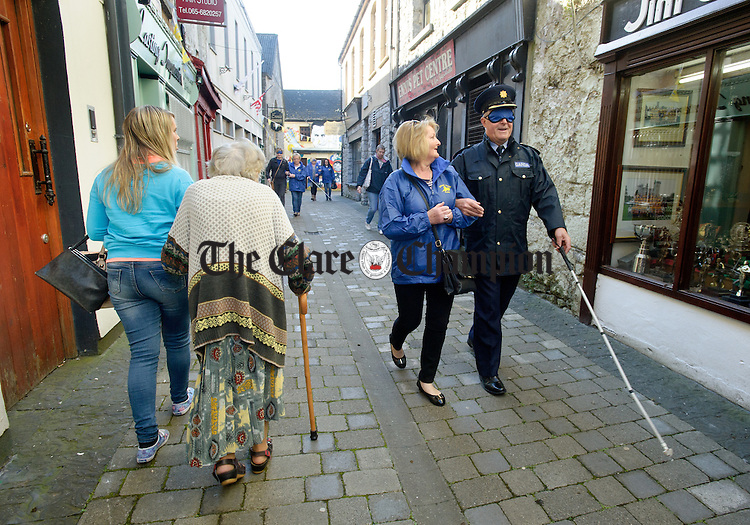 Lena Frazer accompanies Superintendent John Kerin during the Walk A Mile For The Blind event organised by Seeking Vision Clare in Ennis Town centre. Photograph by John Kelly.