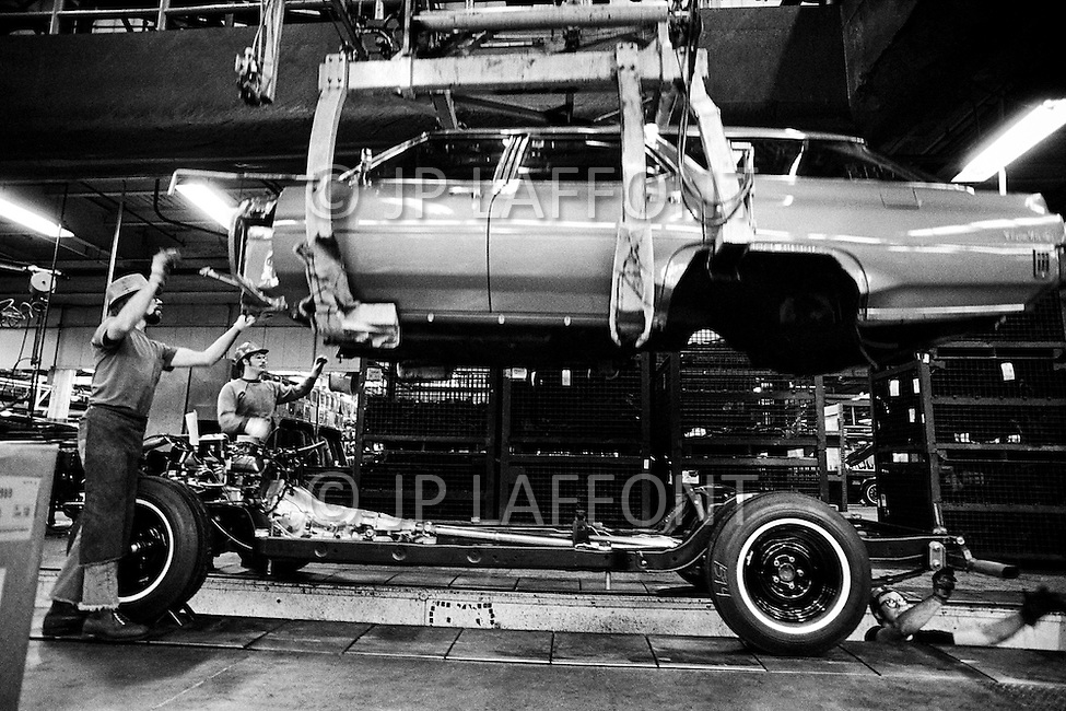 01 Mar 1973, Lansing, Michigan, USA --- Car assembly line at the Oldsmobile factory which was bought in 1908 by General Motors. 20,000 employees churn out 91 vehicles every hour, 16 hours a day, 5-6 days per week, according to demand. The lunch break lasts 30 minutes and is normally taken within the factory complex. Safety glasses are obligatory. --- Image by © JP Laffont