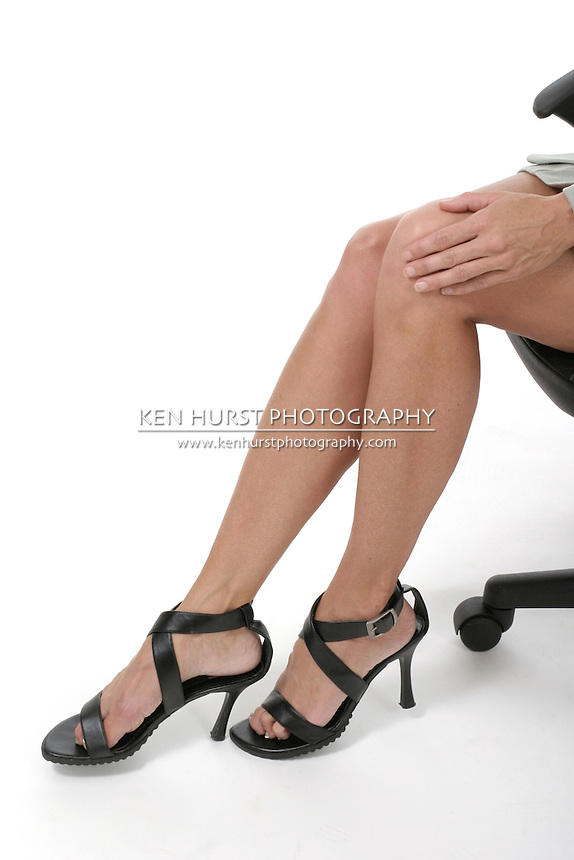 Attractive and sexy but distracting legs of executive business woman sitting in office chair. Portrait orientation. Shot on white.