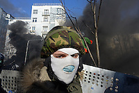 A hodded protester behind the first line of fire in Maidan square. Kiev, Ukraine