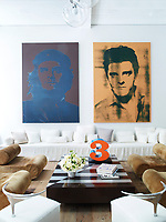 A pair of paintings by Gavin Turk hangs above an Axel Vervoordt sofa in the library; the 1970s suede chairs are by Klaus Uredat, a Robert Indiana sculpture sits atop a vintage French cocktail table. The Philippe Starck chairs in the library were prototypes for the Royalton Hotel. The 18th-century floorboards were salvaged from a Pennsylvania farmhouse.