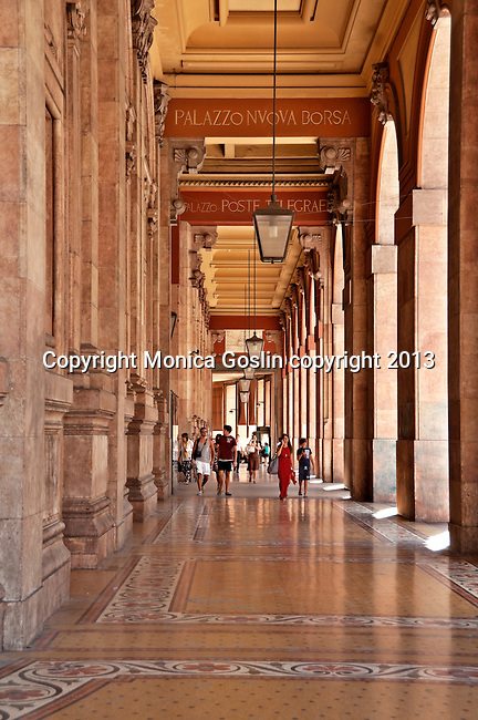 People walking in the shade of the beautifully decorated floors of the arcaded sidewalk around the Palazzo della Nuova Borsa, a large building that sits on one side of the Piazza de Ferrari; summer time