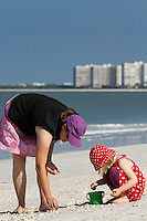 Mother and daughter search for shells in sand at South Beach along Gulf of Mexico, Marco Island, Florida, USA. Photo by Debi Pittman Wilkey