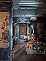 The entrance hall is furnished with an English Indian Colonial nineteenth century armchair and an occasional table made from a nineteenth century Chinese tray. Four hand painted panels, taken from a Chinese screen, have been applied into the wooden panels on the walls