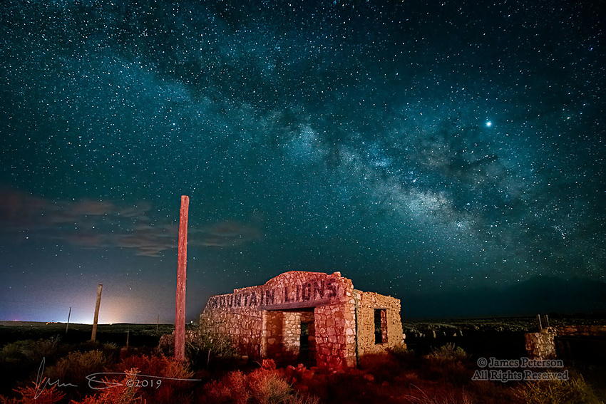 The Zoo at Two Guns, Arizona.  To attract tourists traveling Route 66, the long since abandoned town of Two Guns created a small zoo which proudly advertised the mountain lions featured therein.  Not much is left of the town now, but the ruins make for interesting and slightly spooky photos when the Milky Way is overhead.  The city lights of Winslow, around 25 miles to the east, put a glow on the horizon and also illuminate some clouds on the left in this photo.<br /> <br /> Image ©2019 James D. Peterson.