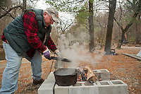 Fairmount Park maintainence worker and FOW volunteer Steve Okula checks on the roasting chestnuts at the Winter in the Wissahickon event. (Dave Tavani/for NewsWorks)