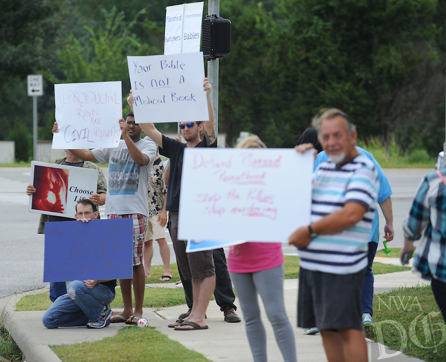 NWA Democrat-Gazette/ANDY SHUPE<br /> Residents hold signs Saturday, Aug. 22, 2015, as nearly 200 people gathered to protest in front of the Planned Parenthood office 3729 N Crossover Road in Fayetteville. The protest was a part of a national effort to call for the defunding of the organization.