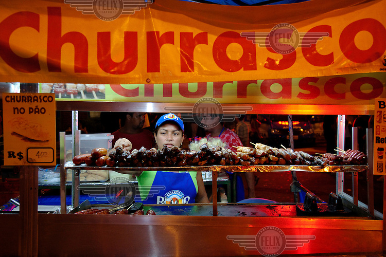 A street vendor selling churrasco (barbequed meats) to the night time crowds in the Lapa neighbourhood.