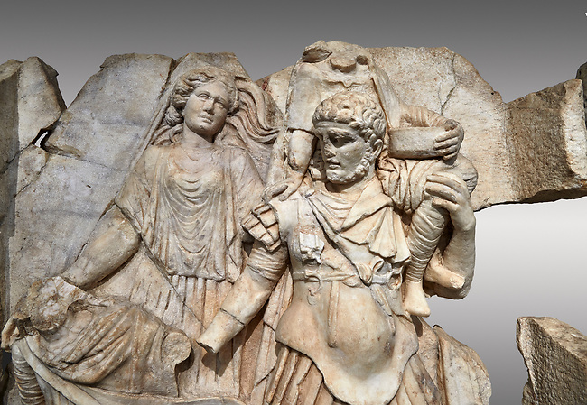 Close up of a Roman Sebasteion relief  sculpture of Aineas' flight from Troy, Aphrodisias Museum, Aphrodisias, Turkey. <br /> <br /> Aineas in armour carries his aged farther Anchises on his shoulders and leads his young son Lulus by his hand. They are fleeing from the sack of Troy. The figure floating behind is Aphrodite, Aineas' mother: she is helping their escape. Old Anchises carries a round box that held images of Troy's ancestral gods.