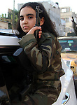 A Palestinian girl wears the al-Qassam Brigades costume during a military parade marking the first anniversary of the killing of Hamas's military commanders Mohammed Abu Shamala and Raed al-Attar, in Rafah in the southern Gaza Strip on August 21, 2015. Abu Shammala and al-Attar were killed by an Israeli air strike during the 50-day war between Israel and Hamas militants in the summer of 2014. Photo by Abed Rahim Khatib