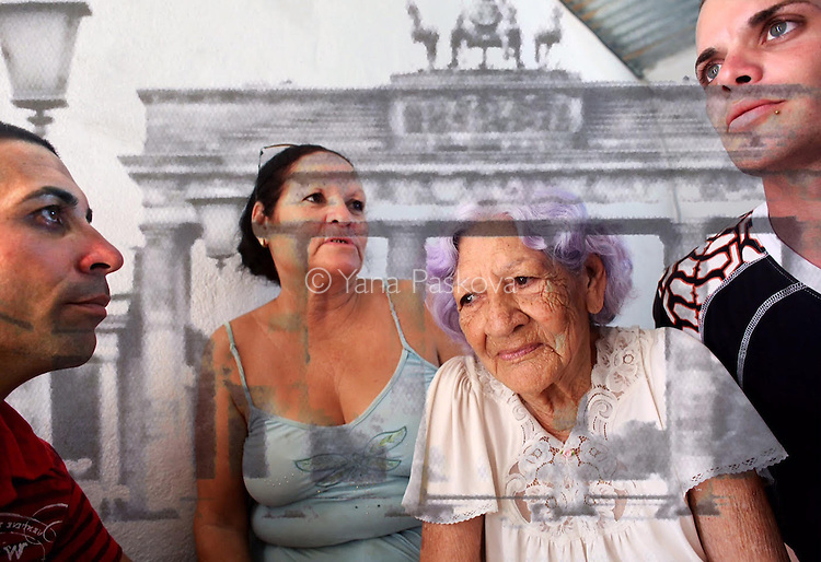This is the Cuban family (sister, nephews and 93-year-old mother) of a man who fled from Cuba to Florida during the Mariel Boatlift of 1980. The four have been separated from their uncle, son and brother for 35 years. It is blended with a faraway view of the Brandenburg Gate, as close as you could get from East Berlin before the fall of the Berlin Wall - photographed during one of few vacations my grandparents and father could take in the Communist years. International travel was limited to pre-approved countries within the Eastern Bloc (while Western nations were accessible with government approval only.) The merging of these images speaks of both the desire for and difficulty of emigration in repressed sociopolitical climates.  <br />