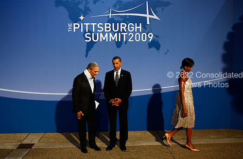 Pittsburgh, PA - September 24, 2009 -- United States President Barack Obama (C) greets Saudi Arabia's Minister of Foreign Affairs Saud Al Faisal (L) at the welcoming dinner for G-20 leaders at the Phipps Conservatory as U.S. first lady Michelle Obama walks away on Thursday, September 24, 2009 in Pittsburgh, Pennsylvania. Heads of state from the world's leading economic powers arrived today for the two-day G-20 summit held at the David L. Lawrence Convention Center aimed at promoting economic growth.  .Credit: Win McNamee / Pool via CNP