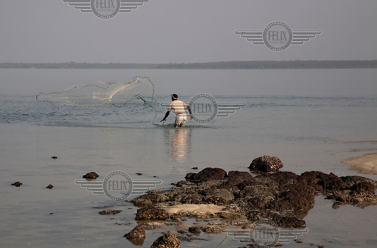A local fisherman throws his net on the island of Angurama.