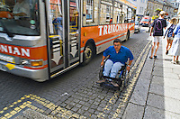 Wheelchair user having to use the road until a suitable location to mount the pavement is found. This image may only be used to portray the subject in a positive manner..©shoutpictures.com..john@shoutpictures.com