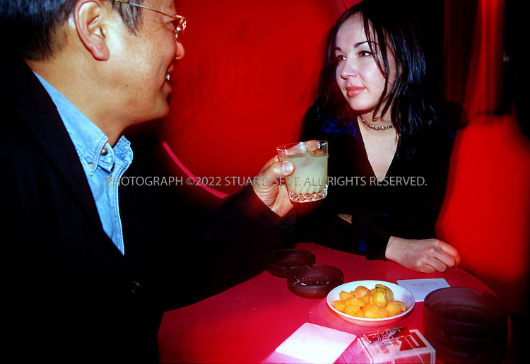 3/6/2002--Tokyo, Japan..At the Flamingo Bar in Tokyo's Roppongi district a British hostess entertains a Japanese customer....All photographs ©2003 Stuart Isett.All rights reserved.This image may not be reproduced without expressed written permission from Stuart Isett.
