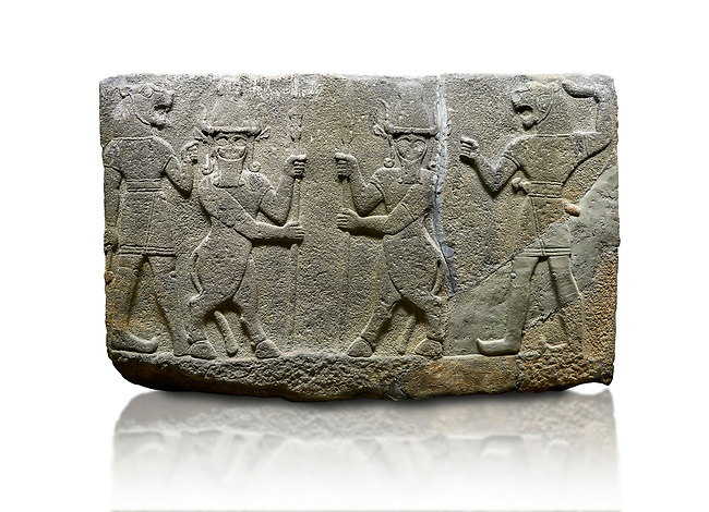 Picture & image of Hittite relief sculpted orthostat stone panel of Herald's Wall. Basalt, Karkamıs, (Kargamıs), Carchemish (Karkemish), 900-700 B.C. Anatolian Civilisations Museum, Ankara, Turkey.<br /> <br /> Protective mixed creatures. One each hand of the lion-headed men is in the form of a fist. The mace on the left is over the head of the weapon on the right. The two bull-men in the middle carry one spear each in their hands. Bull-man is known as Kusarikku, and the lion-man is known as Ugallu. <br /> <br /> Against a white background.