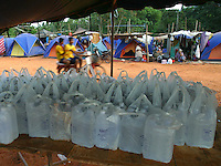 "Koh Lanta, Thailand--Bottled water supplied by the Thai government sits on a communal table waiting to be distributed to Hua Laem residents who lost their homes to the Tsunami on Koh Lanta Island, Thailand.  In the background are the tents provided by ""World Vision"" which many of the villagers have been living in since the Tsunami hit December 26th.  Some residents stay in the tents, which are on the hill above their town, because they fear another Tsunami may come. 01/20/05 © Julia Cumes / The Image Works"