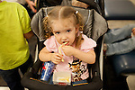 Tabitha Ferrill eats french fries with her siblings at Gate A29 at Hartsfield–Jackson Atlanta International Airport, in Atlanta, Georgia on August 28, 2013.