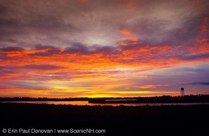 Sunrise over the salt marshes at Hampton Beach, New Hampshire on a cloudy day. A water tower can be seen on the right.