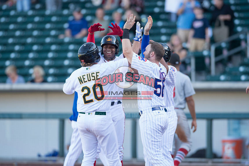 Mesa Solar Sox designated hitter Sheldon Neuse (20), of the Oakland Athletics organization, is congratulated by Kelvin Gutierrez (21), Ian Rice (56), and Charcer Burks (1), after hitting a two-run walk-off home run during an Arizona Fall League game against the Surprise Saguaros on November 2, 2017 at Sloan Park in Mesa, Arizona. The Solar Sox defeated the Saguaros 8-6. (Zachary Lucy/Four Seam Images)