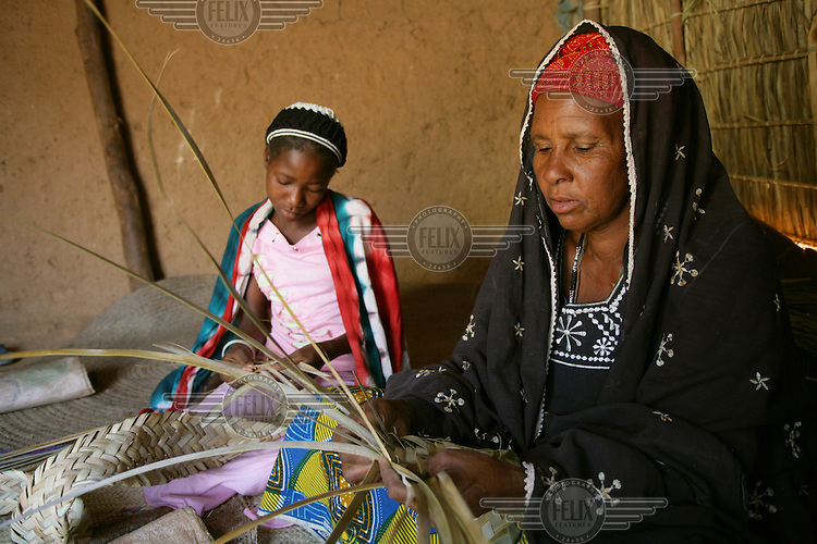 Tanalher, aged 11, helping her mother to weave a mat.