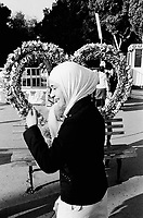 Azerbaijan. Baku Region. Baku. Town center. A young muslim woman, wearing a hidjab to cover her hair, laughs near a heart made of fake plastic flowers on the Boulevard and the National Park. Heart-shaped floral arrangement. © 2007 Didier Ruef