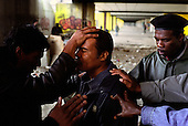 Former drug addicts pray for a junky in a disused construction site Amsterdam. ..The group is part of Victory Outreach, a church started in Los Angeles in 1967. It builds its membership among junkies, prostitutes and criminals. ..Photo taken in the Netherlands in 2002. The picture is part of a photo and text documentary by Justin Jin. For more information, email justin@justinjin.com